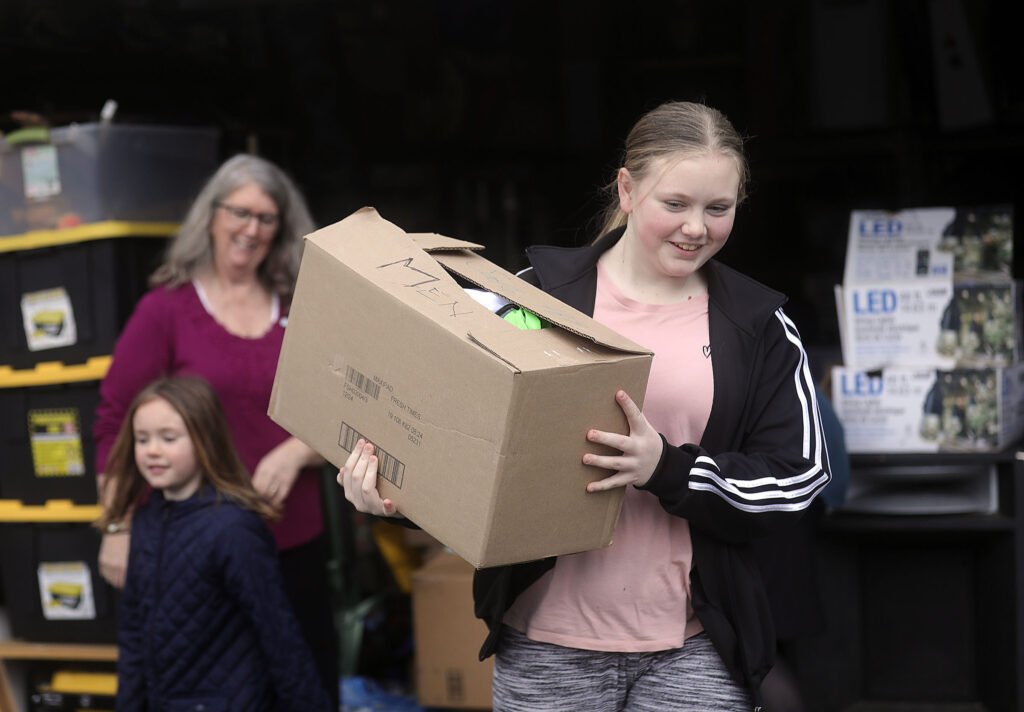 Jordan Wilkie carries a box of hygiene kits from South Hill Stake Relief Society president Mauri Crandall's garage to her grandmother's car, to donate to homeless in Puyallup, Wash., on Sunday, Jan. 26, 2020.
