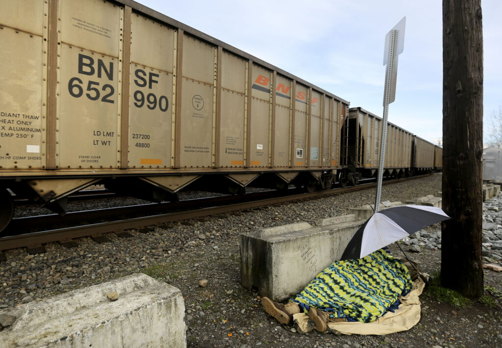 A homeless person sleeps as a freight train passes in Puyallup, Wash., on Saturday, Jan. 25, 2020.