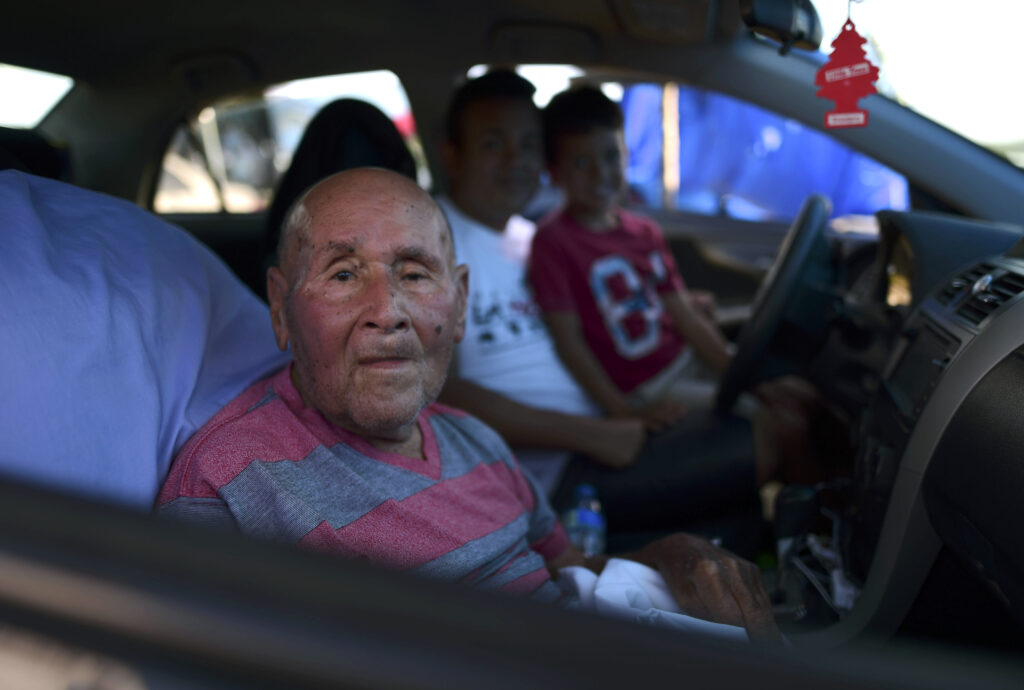 In this Friday, Jan. 10 photo, 83-year-old Angel Luis Pacheco sits with family inside a car parked on a hay farm where residents from the Indios neighborhood of Guayanilla, Puerto Rico, have set up shelter after earthquakes and amid aftershocks in Guayanilla, Puerto Rico. A 6.4 magnitude quake that toppled or damaged hundreds of homes in southwestern Puerto Rico is raising concerns about where displaced families will live, while the island still struggles to rebuild from Hurricane Maria two years ago. (AP Photo/Carlos Giusti)