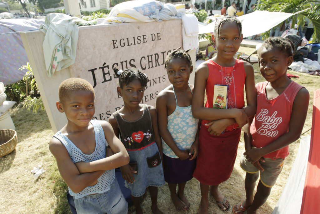 Children stand near the Central Ward meetinghouse sign as they live on the grounds in Port-au-Prince, Haiti, on Jan. 19, 2010, a week after a 7.0-magnitude earthquake hit the region.