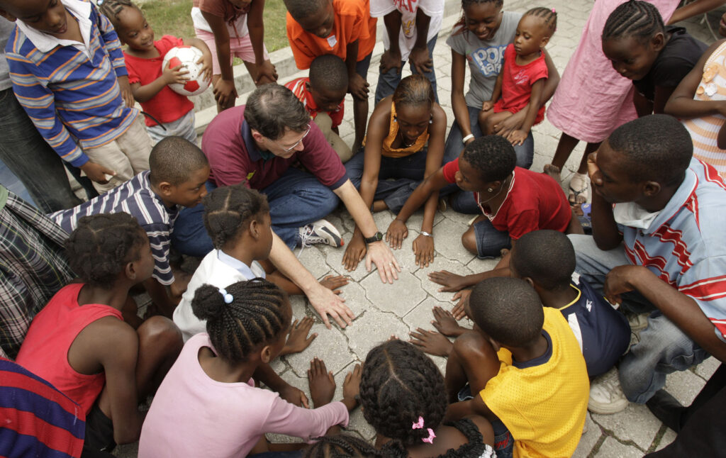 Family Services specialist Paul Garrett plays hand games with Haitian children in Port-au-Prince, Haiti, on Jan. 19, 2010. A 7.0-magnitude earthquake hit the region 7 days earlier.
