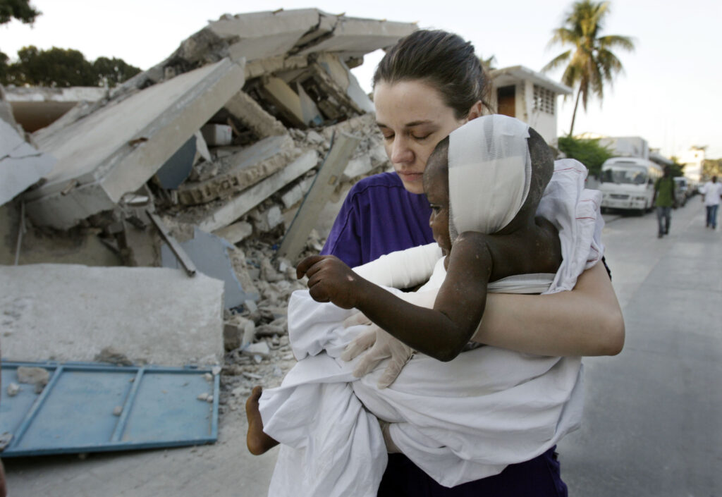 Latter-day Saint nurse Elizabeth Howell carries 4-year-old Oresto Oclor to hospital for surgery on the boy's arm in Port-au-Prince, Haiti, on Jan. 22, 2010. Howell, along with other Utah doctors, treated the boy and transported him to the nearest hospital.