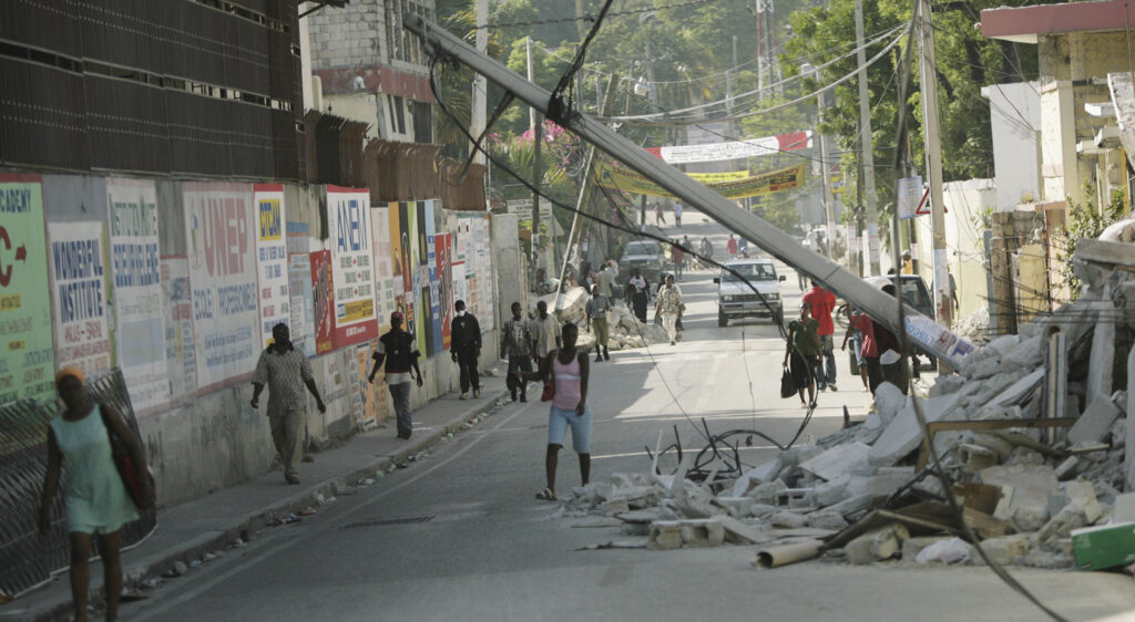 Haitians walk near the rubble of collapsed buildings and power lines in Port-au-Prince, Haiti, on Jan. 19, 2010 — a week after a 7.0 magnitude earthquake struck the region.