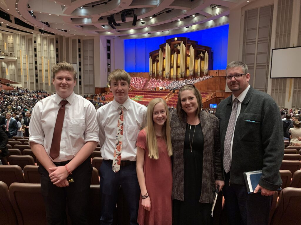 Drew Haley, far left, attends a session of general conference with his family, from left, Brayden, Ella, Alison and Matt Haley.