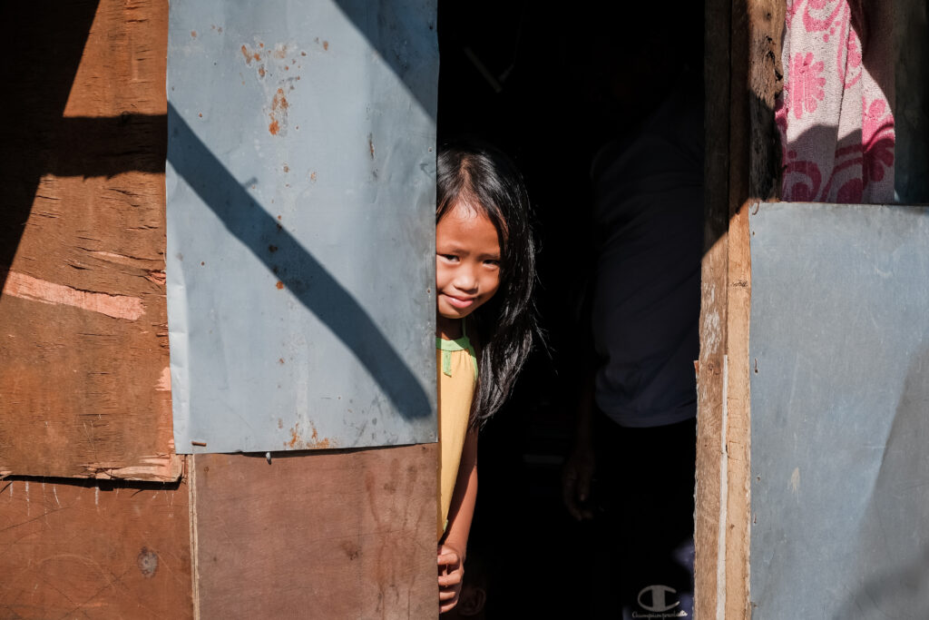 A young girl pokes her head out of her front door in Catarman, Philippines, on Feb. 3, 2020. Sister Jean B. Bingham visited families in the area to learn about a stake pilot program focused on addressing malnutrition in the area.