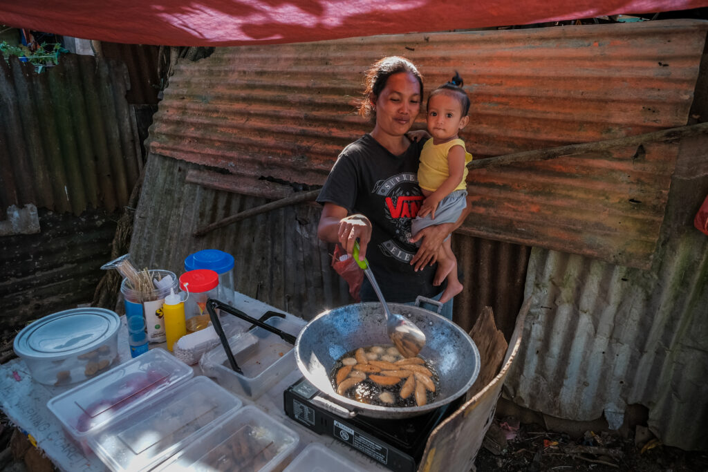 A mother cooks food outside her home in Catarman, Philippines, on Feb. 3, 2020, during a visit from Sister Jean B. Bingham.