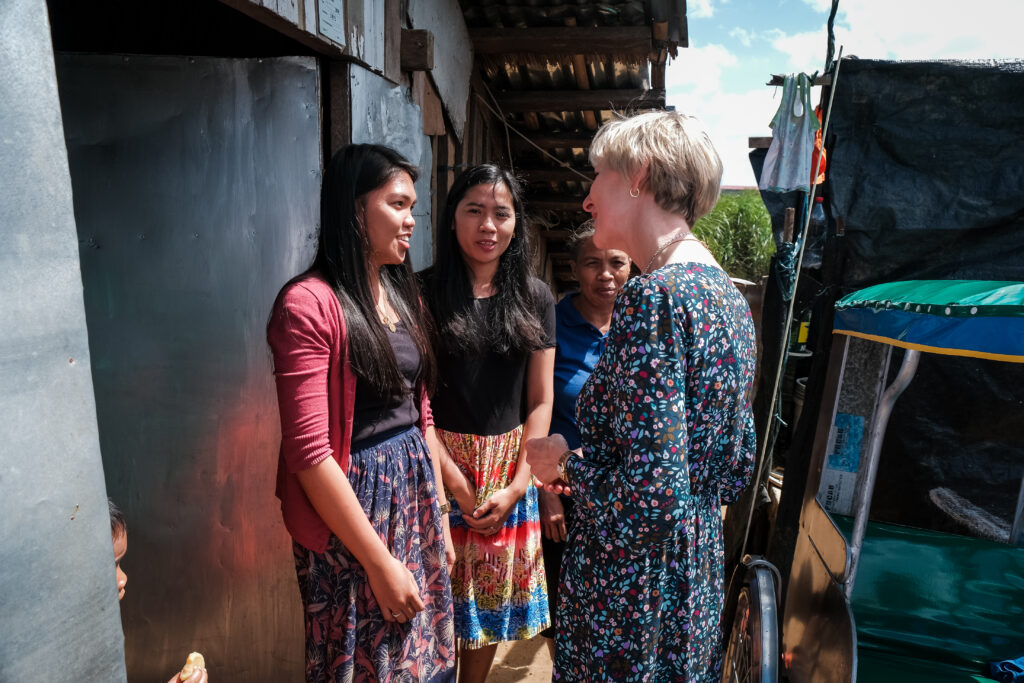 Sister Jean B. Bingham speaks with Charlene Lagrimas, left, and Maribel Chu, center, outside of the home of a family they minister to as part of a stake pilot program focused on malnutrition in Catarman, Philippines, on Feb. 3, 2020.