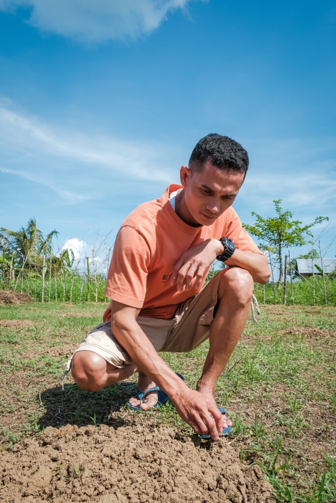 Franco Batiles crouches over a mound of dirt in his garden in Catarman, Philippines, on Feb. 3, 2020, to show visitors the new sprouts popping up after his garden was destroyed by Typhoon Tisoy in December 2019.