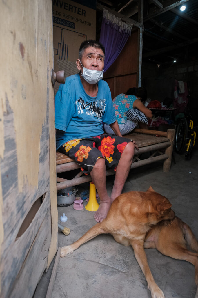 Jorge Alvarez, a member of the Lemery Philippines Branch, sits by his front door after returning home for the first time in three weeks on Feb. 6, 2020, after having to evacuate following the Jan. 12 eruptions of the Taal Volcano.