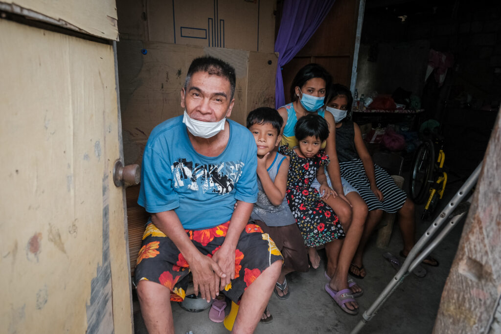 Jorge Alvarez, a member of the Lemery Philippines Branch, sits by with some of his family members by his front door after returning home for the first time in three weeks on Feb. 6, 2020, after having to evacuate following the Jan. 12, eruptions of thee Taal Volcano.