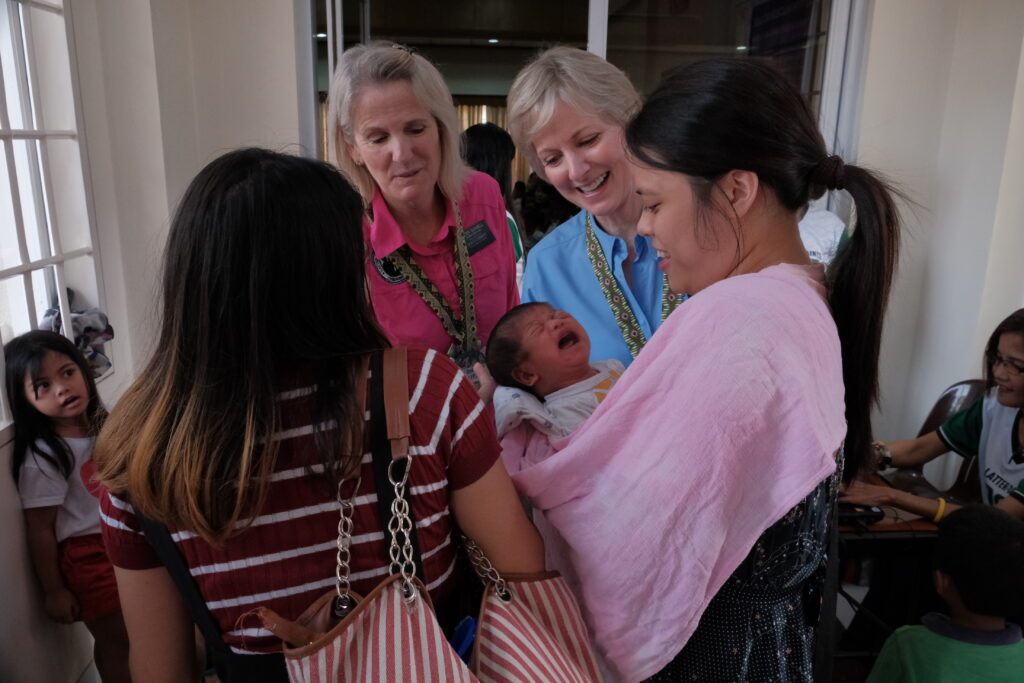 Sister Jean B. Bingham, second from right, greets some of the members in the Toledo Philippines District during a malnutrition screening hosted by the district on Saturday, Feb. 8, 2020.