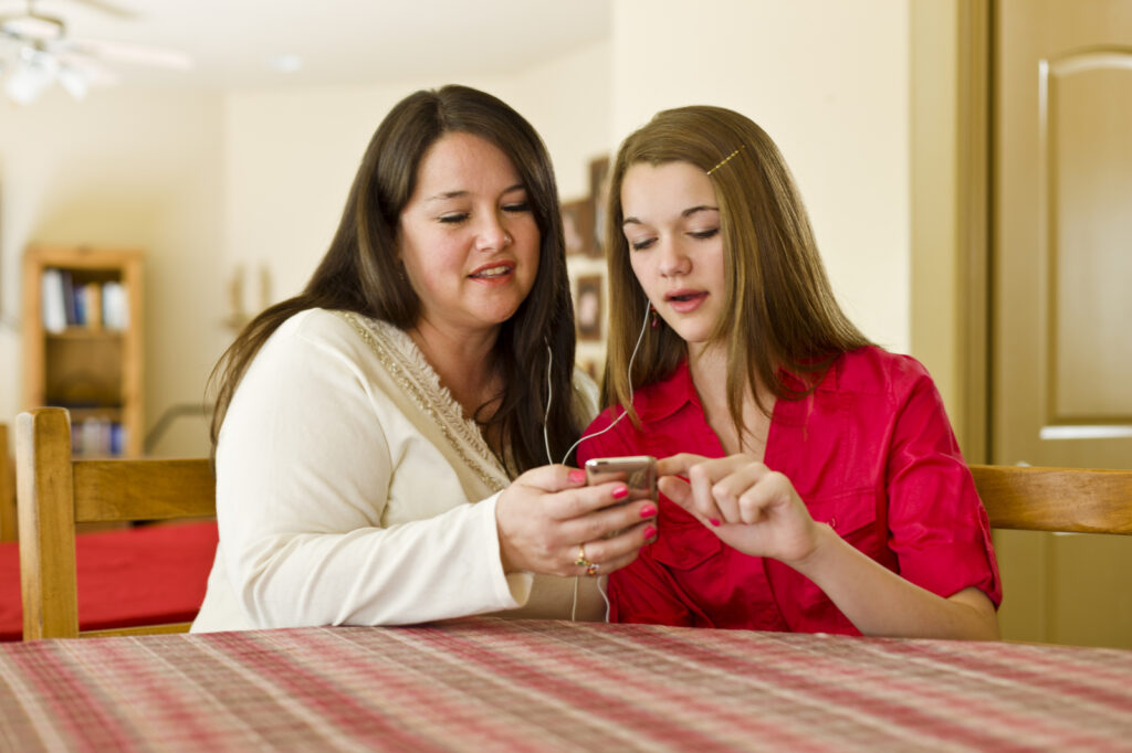 A young woman shows her mother some of the features of the new Gospel Living app while listening to uplifting music.