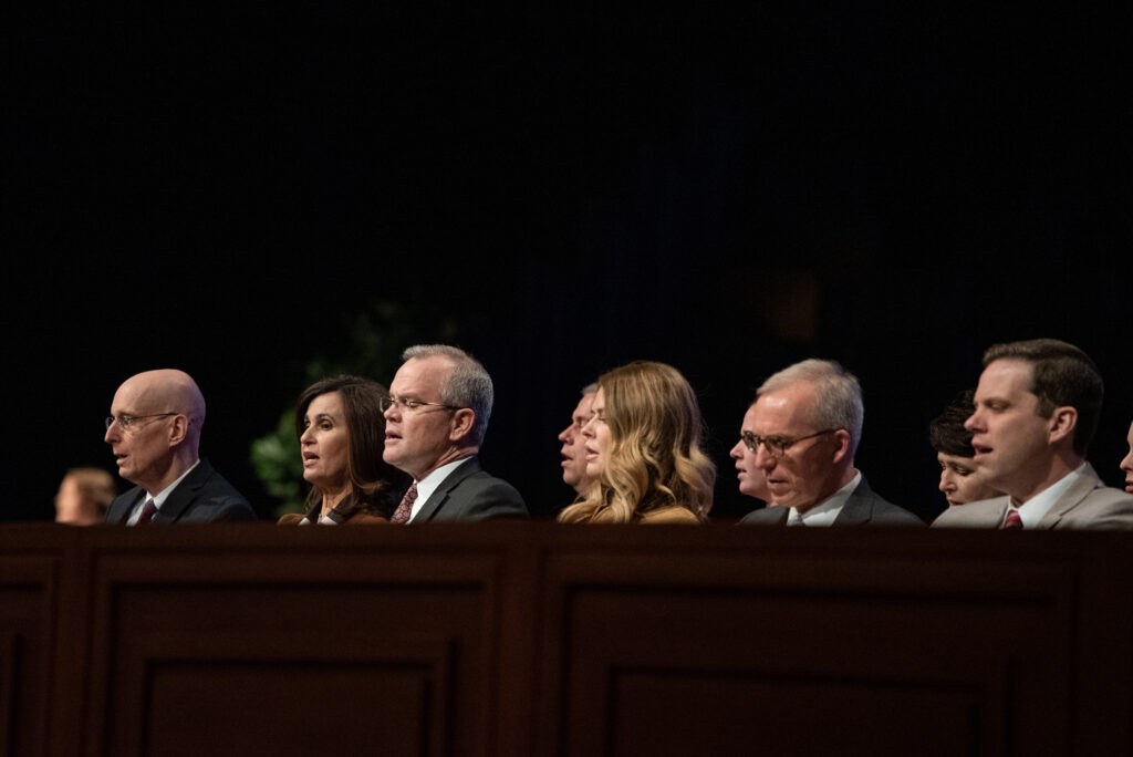 President Henry J. Eyring, left, and Sister Lisa L. Harkness, second left, sing with others seated on the stand during a BYU–Idaho campus devotional on Tuesday, Feb. 11, 2020, in Rexburg, Idaho.