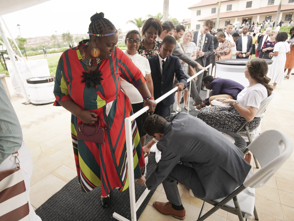 Nhla Dlomo gets shoe coverings placed prior to the Durban South Africa Temple dedication in Umhlanga, South Africa, on Sunday, Feb. 16, 2020.