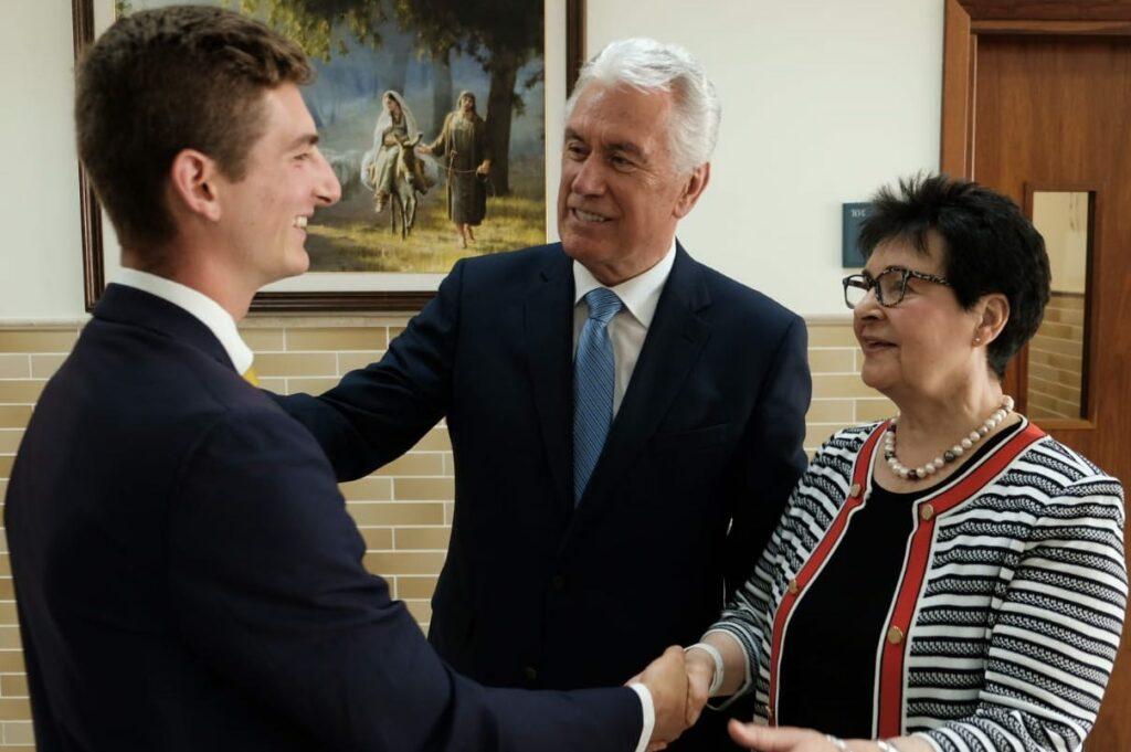El élder Dieter F. Uchtdorf y la hermana Harriet Uchtdorf saludan a un misionero en Montevideo, Uruguay, durante el viaje de febrero de 2020 a América del Sur.