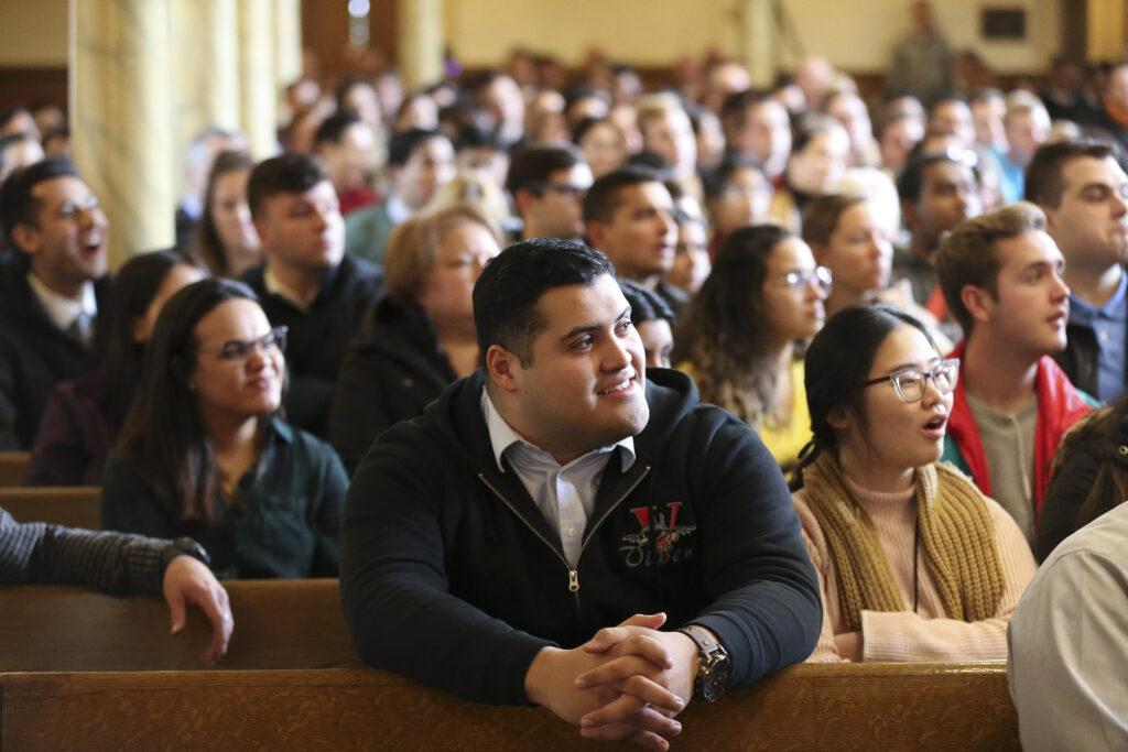 El estudiante de LDS Business College, Sergio Cienfuegos, escucha el anuncio del cambio de nombre de la escuela durante un devocional en el Salón de Asambleas de Temple Square en Salt Lake City el martes 25 de febrero de 2020. El nuevo nombre es Ensign College.