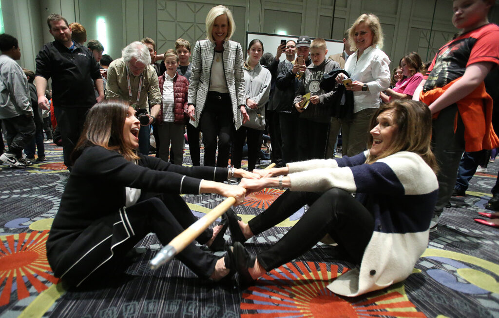 The Young Women general presidency, Sisters Bonnie H. Cordon (center), Becky Craven (left) and Michelle Craig (right), take part in a stick pull as the Young Women and Young Men general presidencies visit the RootsTech youth night at the Salt Palace in Salt Lake City on Wednesday, Feb. 26, 2020.
