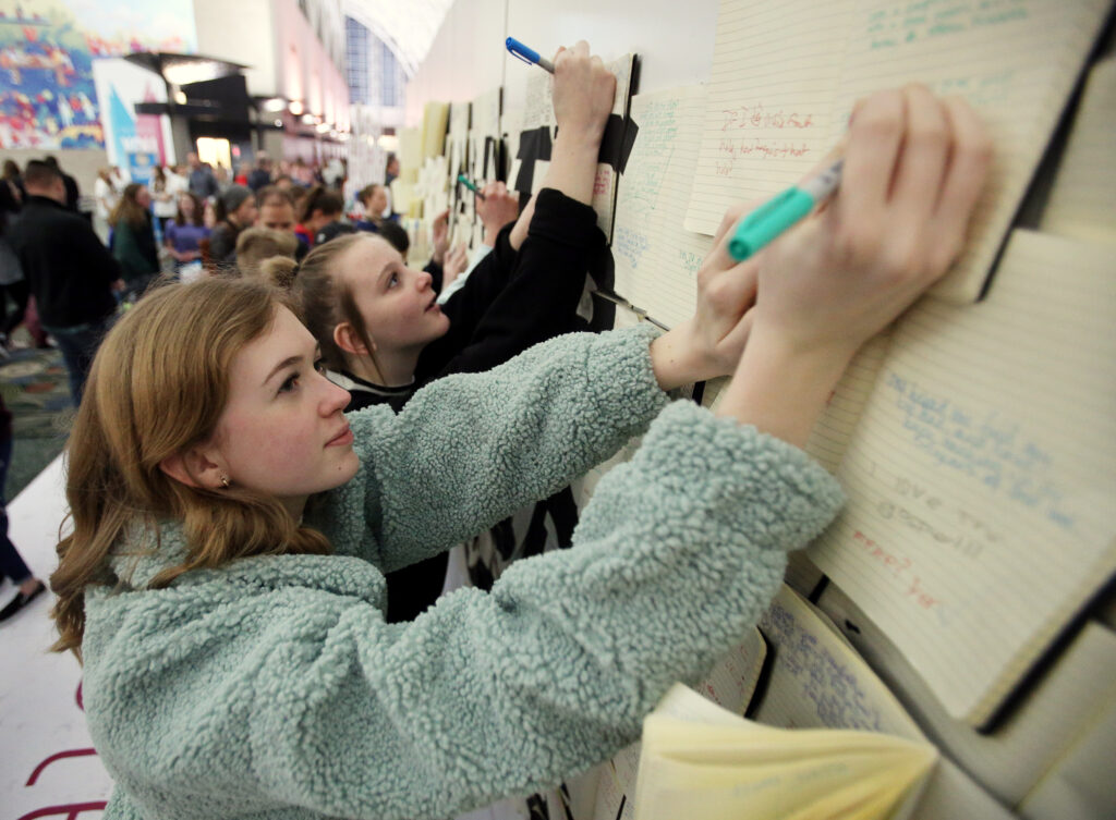 Emily Johnson and Rachael Nufer write their feelings about the Church and what it means to them on notebooks on a wall as attend RootsTech youth night at the Salt Palace in Salt Lake City on Wednesday, Feb. 26, 2020.