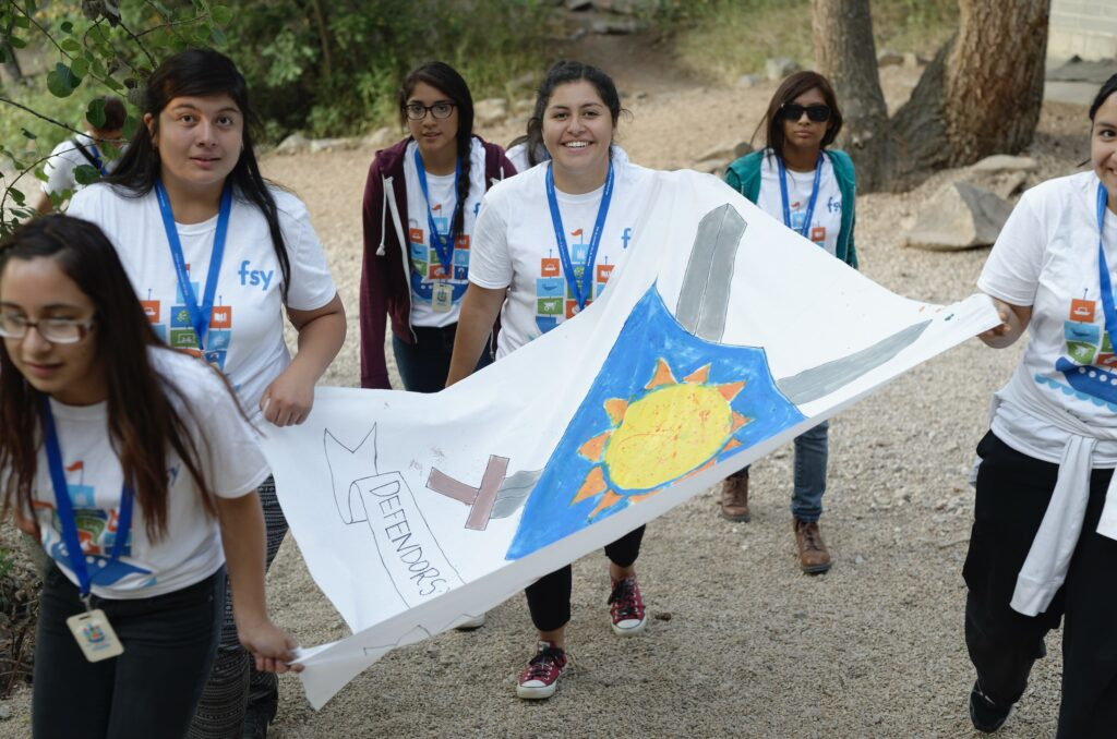 Young members of The Church of Jesus Christ of Latter-day Saints carry a flag during an activity at an FSY conference in 2015.