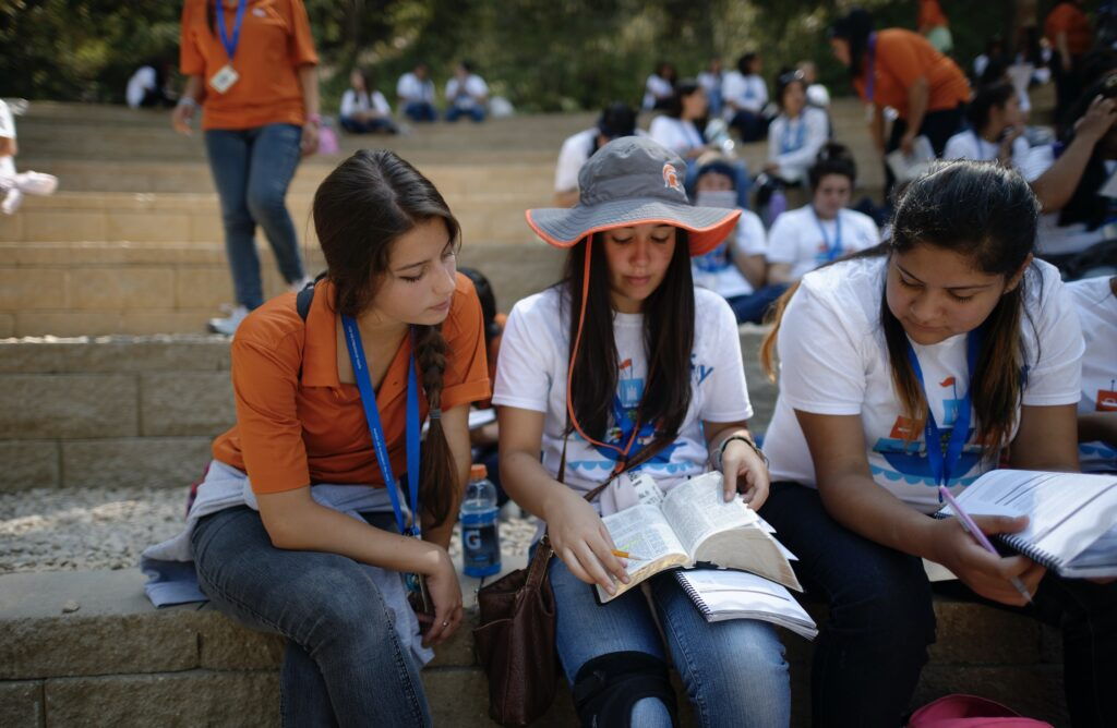 Young women study the scriptures during a For the Strength of Youth Conference in 2015.