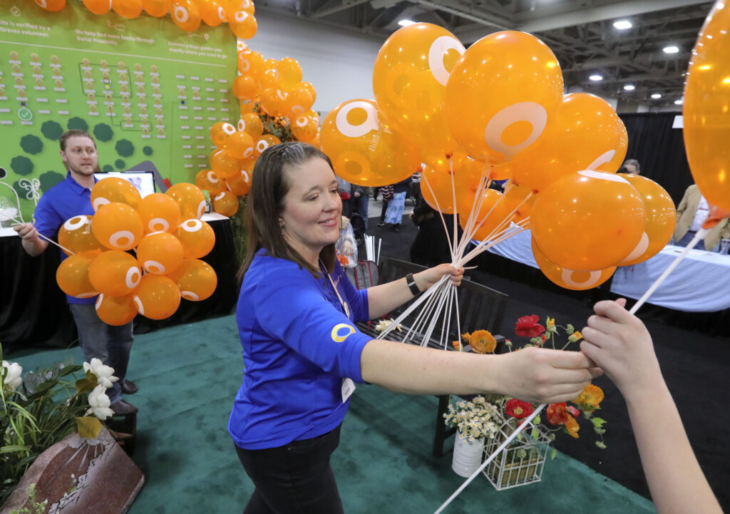 Anna Young hands out balloons at the BillionGraves booth during RootsTech at the Salt Palace Convention Center in Salt Lake City on Saturday, Feb. 29, 2020.