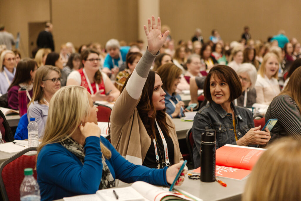 An attendee raises her hand at Light Keepers, a RootsTech event for Latter-day Saint women at the Salt Palace Convention Center in Salt Lake City on Feb. 28, 2020.
