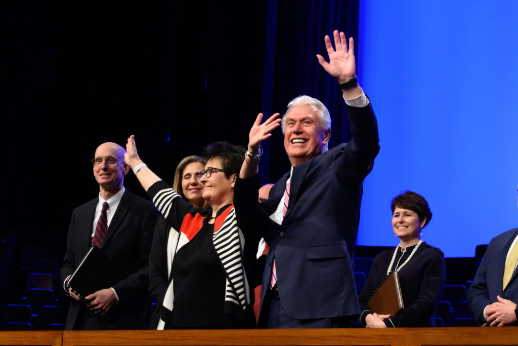 Elder Dieter F. Uchtdorf and Sister Harriet Uchtdorf salute thousands of students gathered inside the BYU-Idaho Center on March 1, 2020, for an evening devotional. They are joined on the podium by BYU-Idaho President Henry J. Eyring, far left, and his wife, Sister Kelly Eyring.
