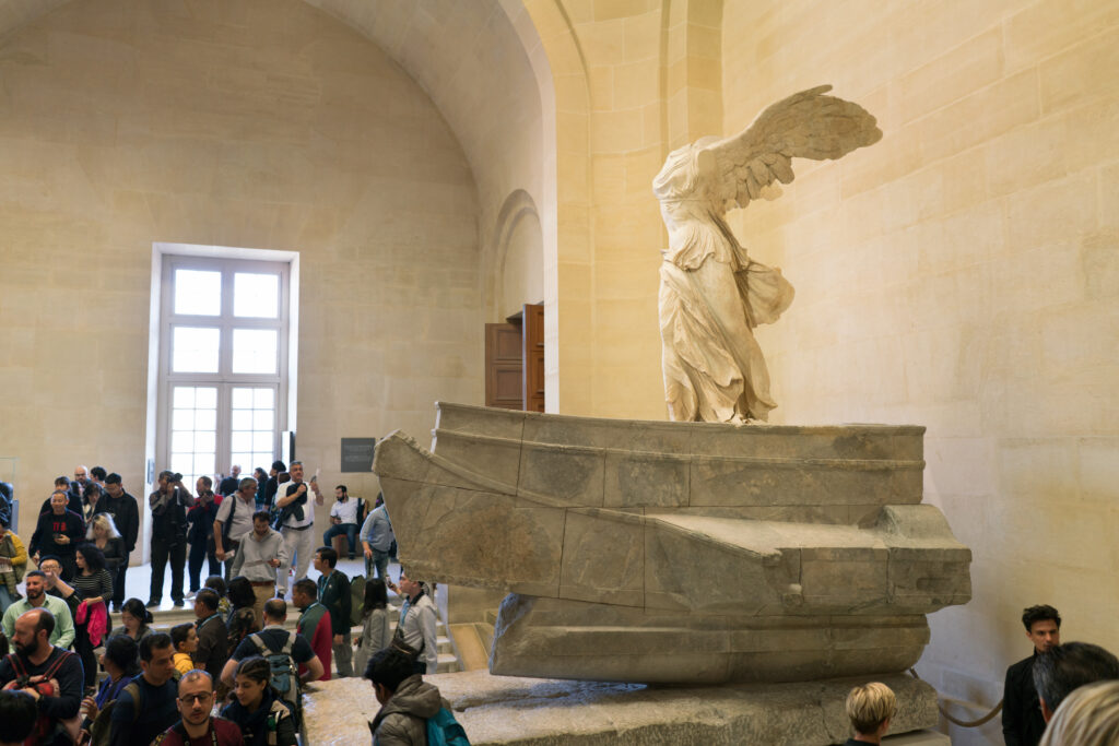 People on stairs look at The Winged Victory of Samothrace at the Louvre Museum in Paris.