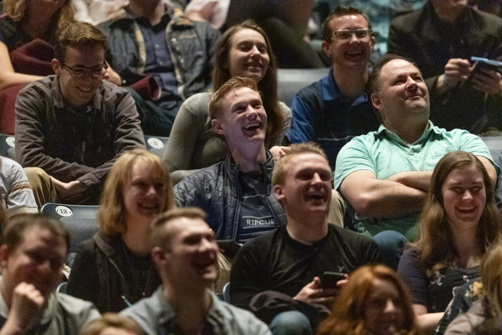 Crowd members laugh as President M. Russell Ballard, acting president of the Quorum of the Twelve Apostles of The Church of Jesus Christ of Latter–day Saints talks about using his smartphone and technology as he speaks at a BYU devotional in the Marriott Center in Provo on Tuesday, March 3, 2020.