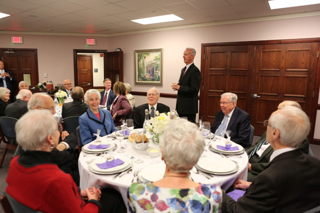 President M. Russell Ballard, acting president of the Quorum of the Twelve Apostles, has dinner with old friends as Michael Finnigan addresses the dinner audience at the Brampton Stake Center in Brampton, Ontario, Canada, March 6, 2020.