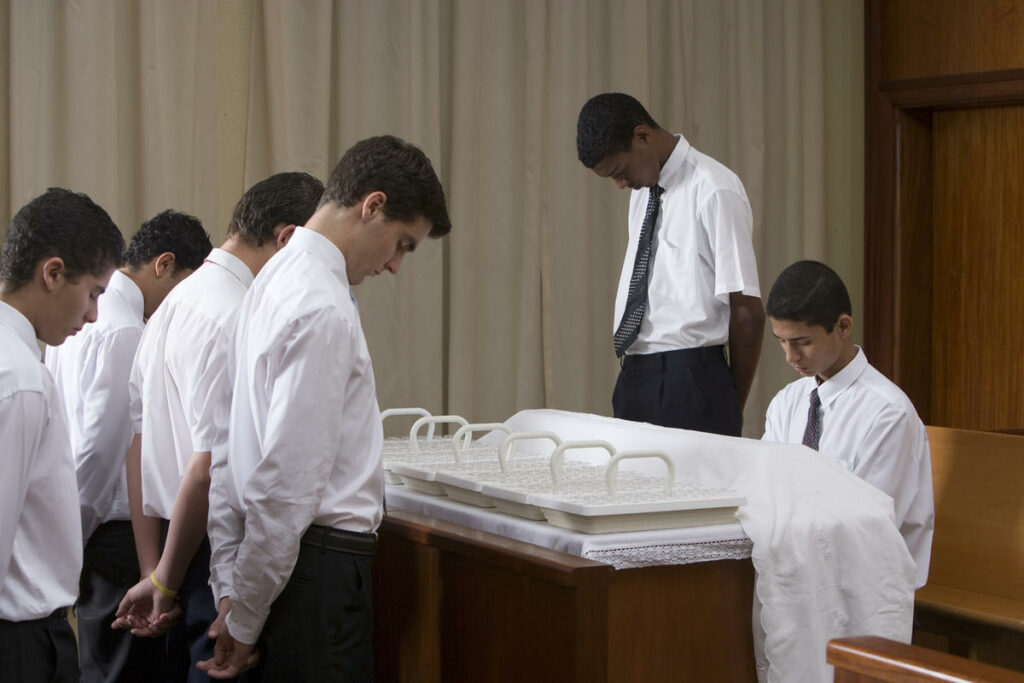 Young men administer the sacrament of bread and water to the congregation.