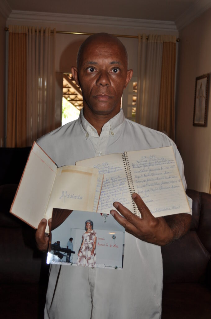 Paulo De Oliveira Lima poses with his mother's diaries and photo in his home near Brasília, Brazil, in 2012.