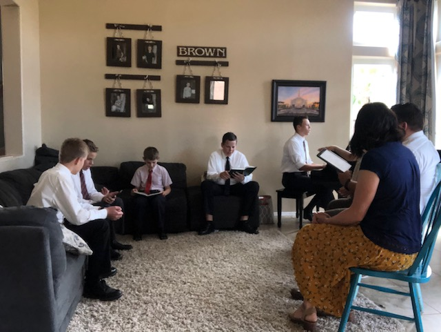 The Brown Family of Gilbert, Arizona, gather in their living room for a home Sabbath day service. Traditional gatherings were cancelled because of the coronavirus pandemic.