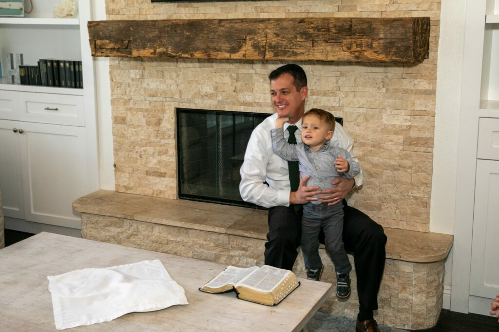 Bishop Darren L. Harline holds his young son as he and his family observe the Sabbath in their home in San Clemente, California, on March 15, 2020, after the Church suspended all meetings in the wake of the COVID-19 pandemic.