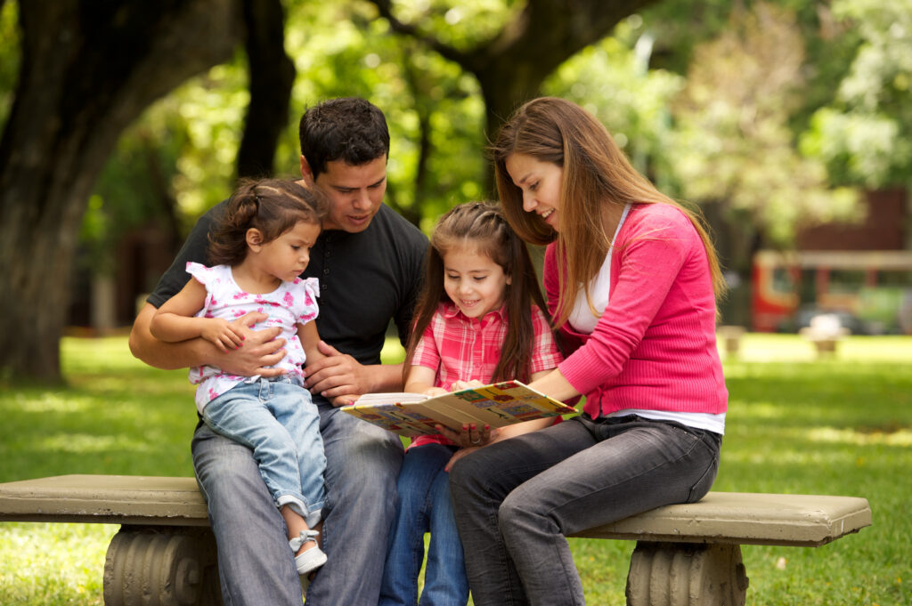A family reads together in a park.