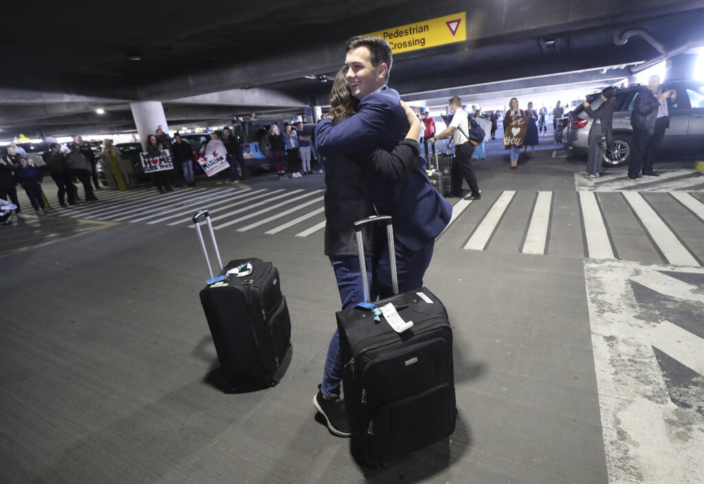 Elder Tyler Barnes hugs family as hundreds of missionaries from The Church of Jesus Christ of Latter-day Saints return from the Philippines to Salt Lake City International Airport on Sunday, March 22, 2020.