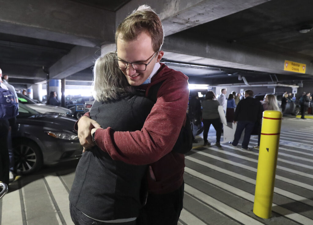 Elder Ammon Jensen is hugged by his mother, Nancy Jensen, as hundreds of missionaries from The Church of Jesus Christ of Latter-day Saints return from the Philippines to Salt Lake City International Airport on Sunday, March 22, 2020.