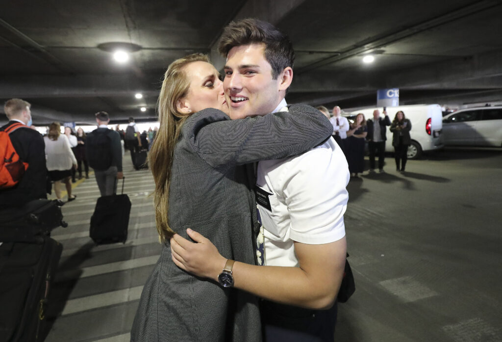 Elder Mason North is kissed by his mother, Kristen North, as hundreds of missionaries from The Church of Jesus Christ of Latter-day Saints return from the Philippines to Salt Lake City International Airport on Sunday, March 22, 2020.