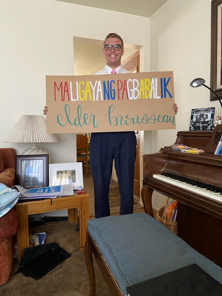 "Elder Stephen Brousseau holds a ""Welcome Home"" sign at his Orem, Utah, home on March 22, 2020, after returning from the Philippines."
