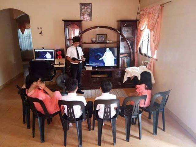 Crisanta Estayo-Padilla's husband shares a message with their family as they worship at home on Sunday, March 15, 2020, in the Philippines.
