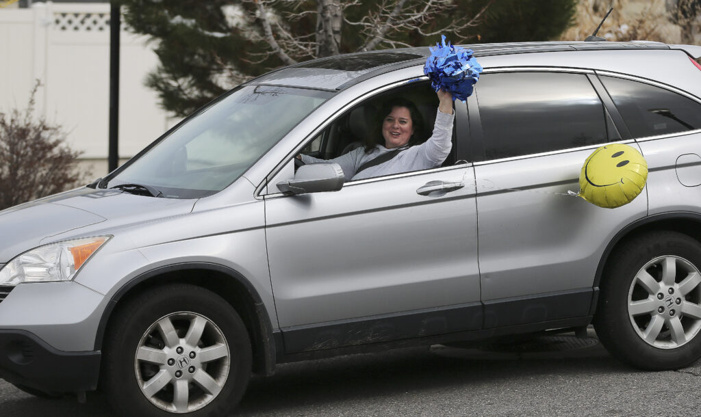"A well wisher waves as friends and neighbors welcome home full-time missionaries during a ""driving tour"" in South Jordan, Utah, on Thursday, March 26, 2020."