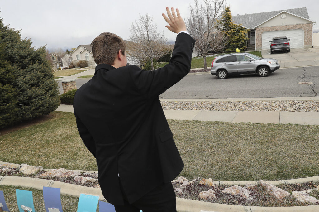 "Elder Bryant Hall waves as friends and neighbors welcome home full-time missionaries during a ""driving tour"" in South Jordan, Utah, on Thursday, March 26, 2020."
