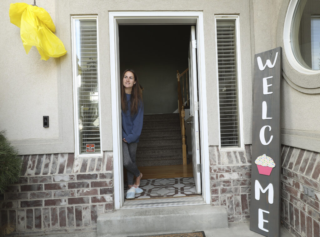 "Sister Kaytlin Telford stands in the door way as friends and neighbors welcome home full-time missionaries during a ""driving tour"" in South Jordan, Utah, on Thursday, March 26, 2020."