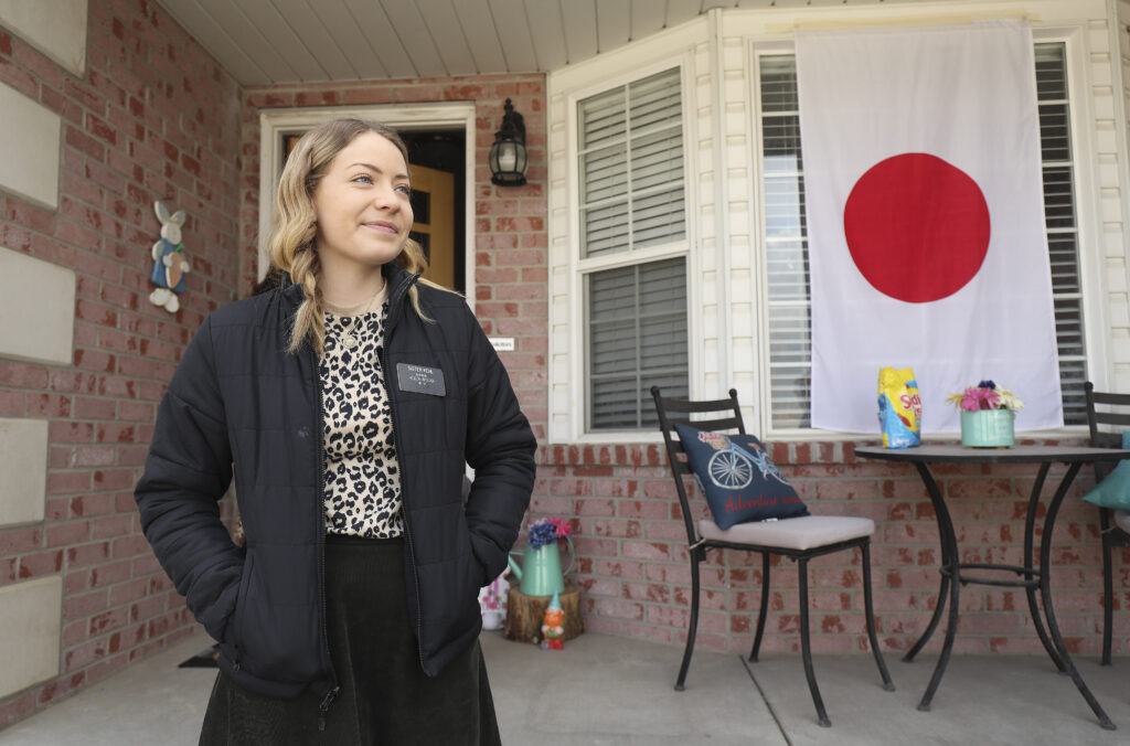"Sister Madison Kehl waits as friends and neighbors welcome home full-time missionaries during a ""driving tour"" in South Jordan, Utah, on Thursday, March 26, 2020."