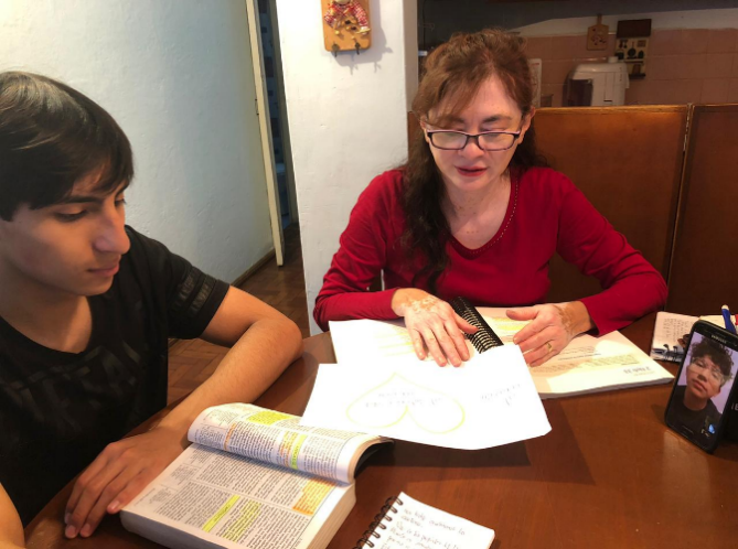 Sister Amparito Oliva, a seminary teacher in Quito, Ecuador, teaches her son, Jeffrey Oliva, and video conferences with Jared Villacrés, another student. She continues to teach face-to-face with her son and using technology, including the program's Facebook page to send assignments that are uploaded daily.