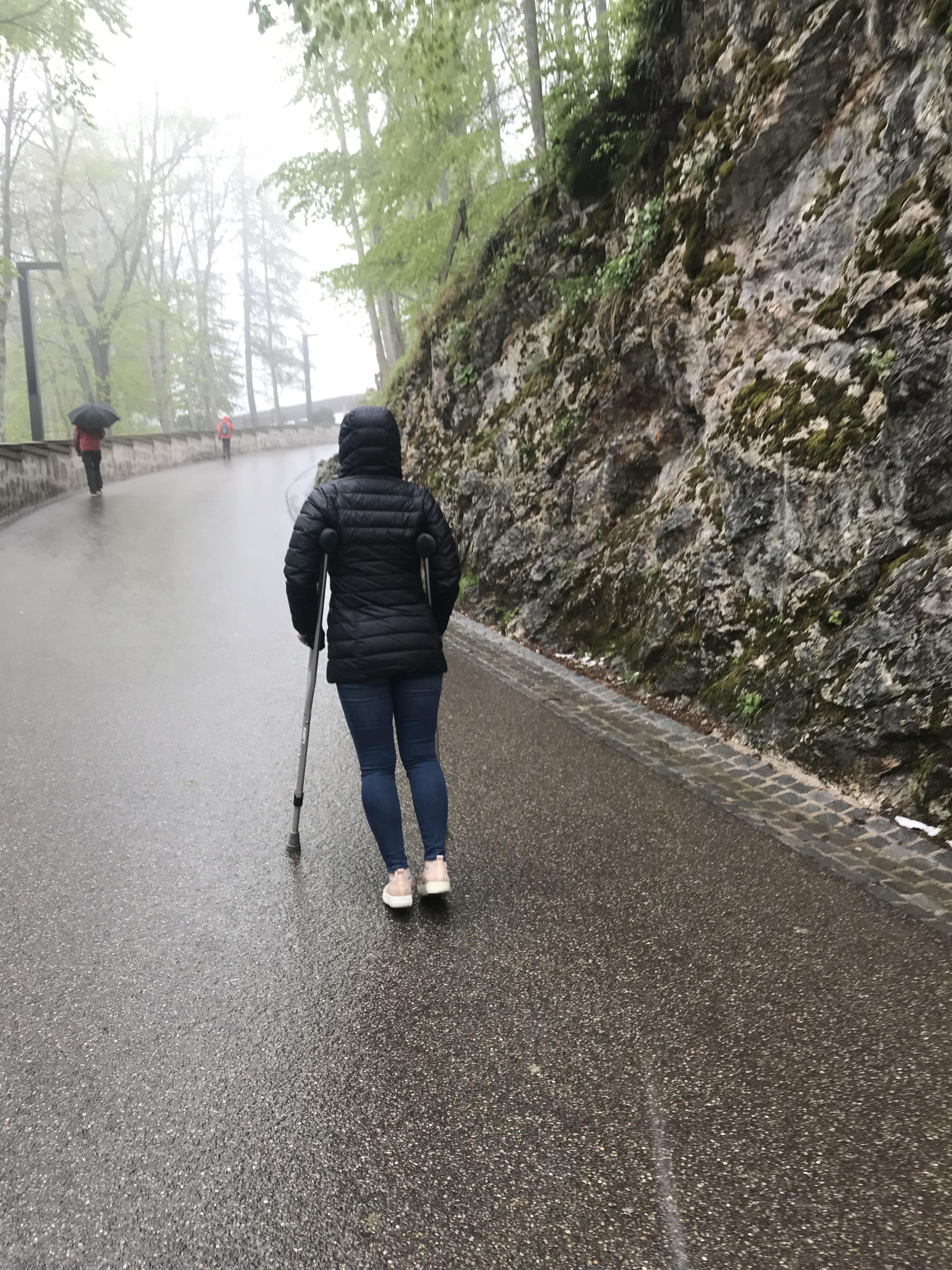 Monique McDown andando com muletas durante uma viagem à Alemanha. A perna direita de McDown ficou paralítica devido a um acidente que sofreu quando servia uma sua missão no Brasil.
