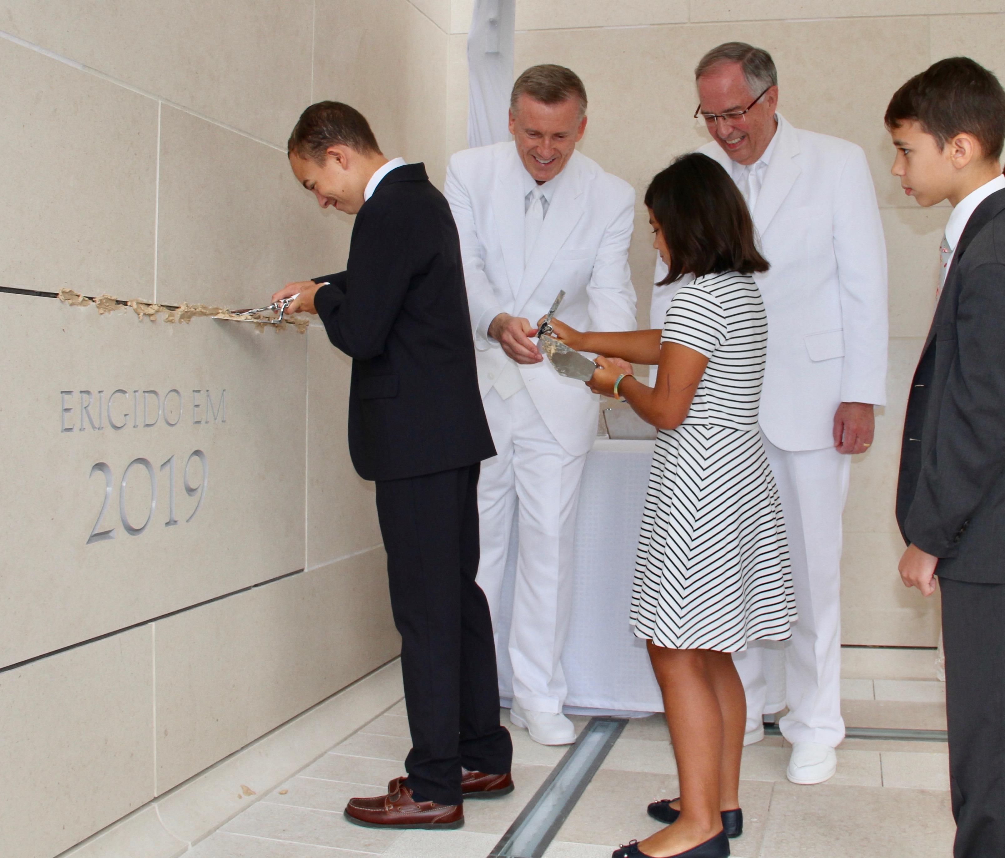 Crianças participam da cerimônia de colocação da pedra angular na dedicação do Templo de Lisboa Portugal no domingo, 15 de setembro de 2019, recebem ajuda do élder Kevin R. Duncan, atrás à esquerda, e do élder Neil L. Andersen, atrás à direita.