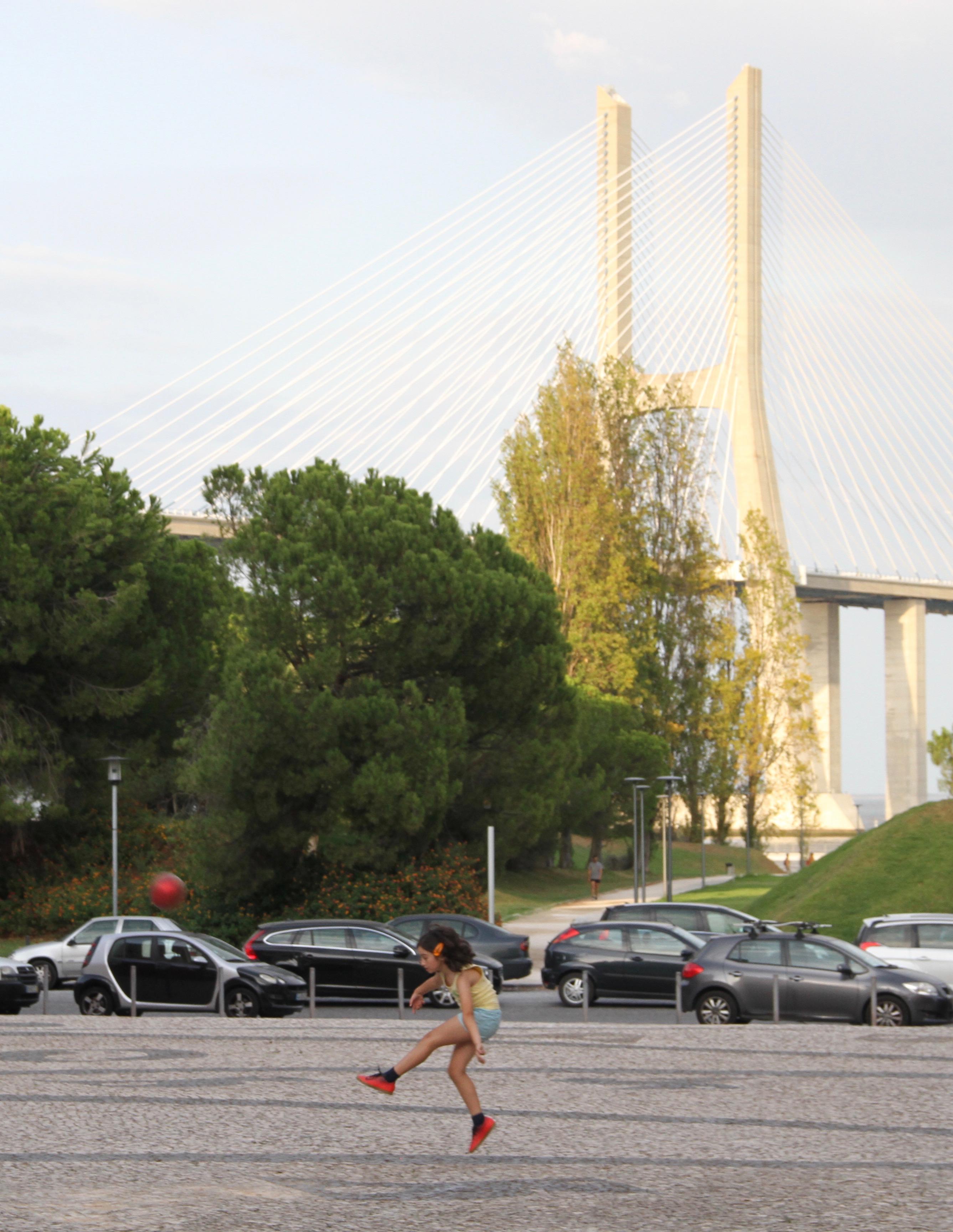 Uma menina chutando uma bola de futebol numa praça perto da Ponte Vasco da Gama sobre o Rio Tejo, no sábado, 14 de setembro de 2019.