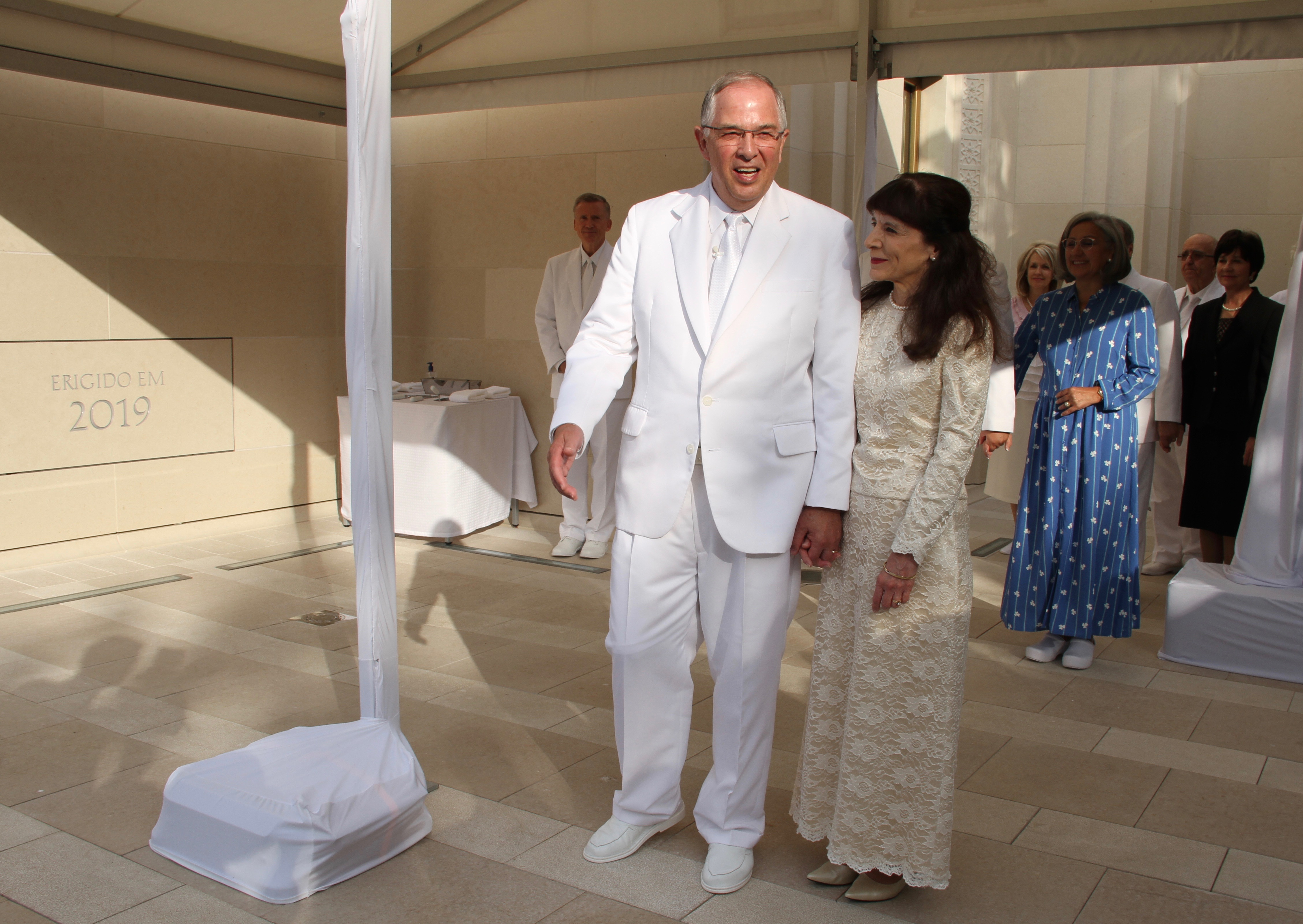 O élder Neil L. Andersen, do Quórum dos Doze Apóstolos, acompanhado por sua esposa, a irmã Kathy Andersen, conversando com membros do lado de fora na cerimônia de colocação da pedra angular na dedicação do Templo de Lisboa Portugal no domingo, 15 de setembro de 2019.