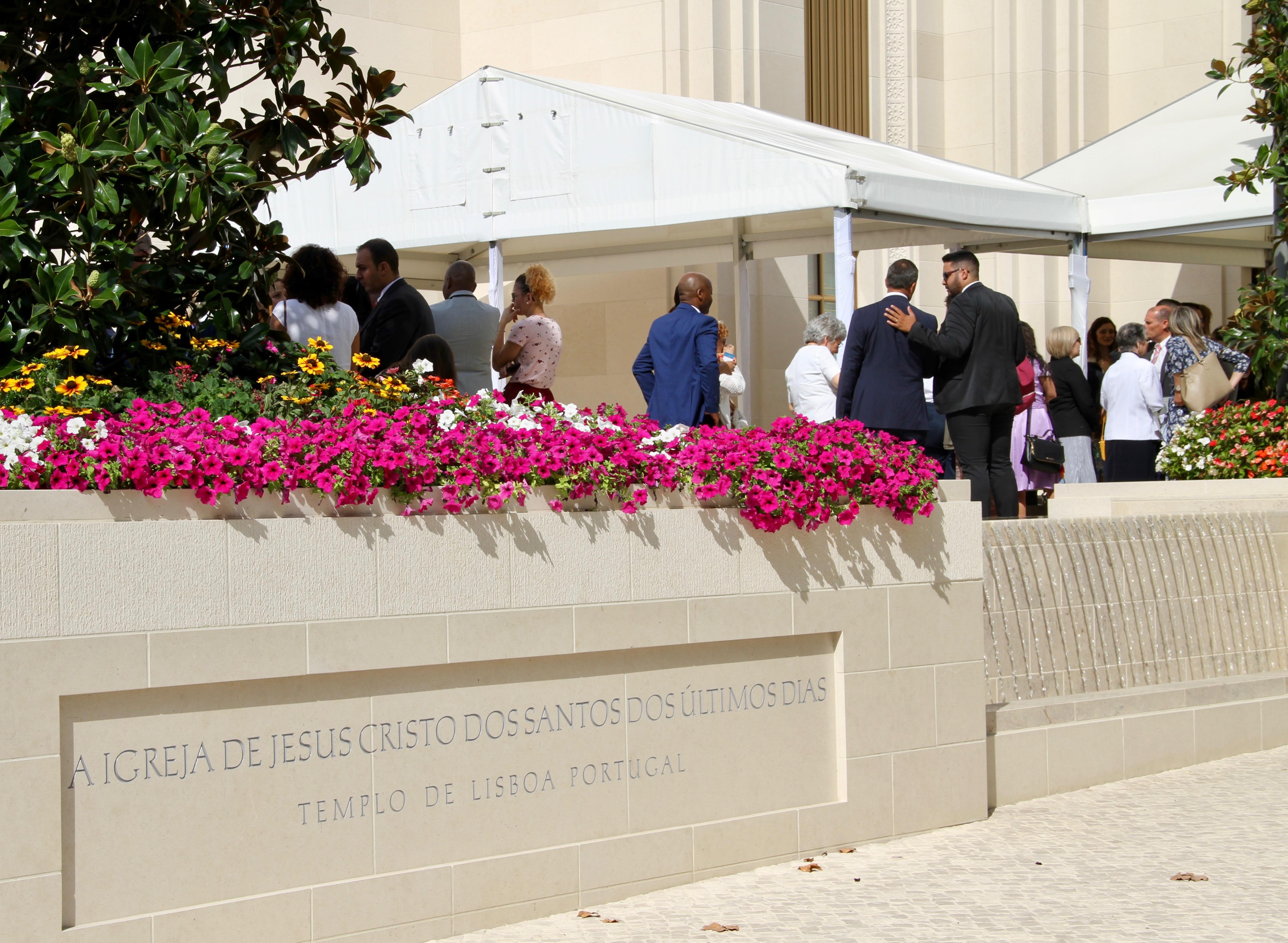 Com a placa do Templo de Lisboa Portugal e uma das fontes em primeiro plano, os membros reúnem-se fora do templo após a primeira sessão dedicatória no domingo, 15 de setembro de 2019.